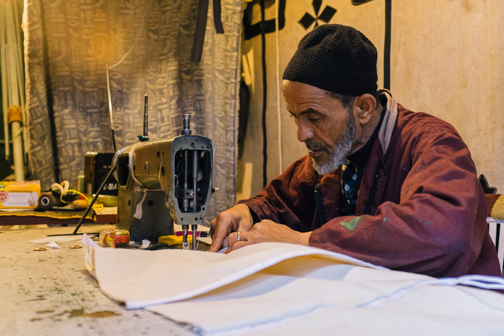 A man sewing a curtain