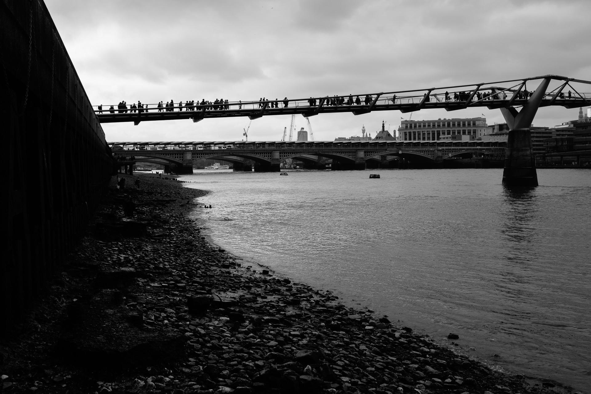 Millenium bridge in London full of people in black and white