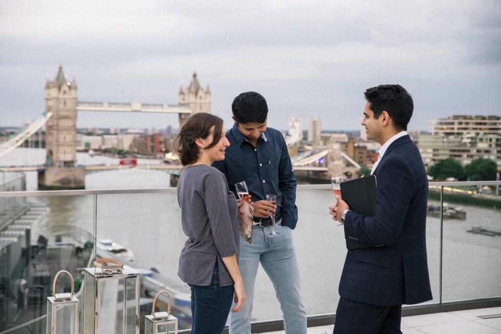 ludzie z drinkami na tle tower bridge w londynie