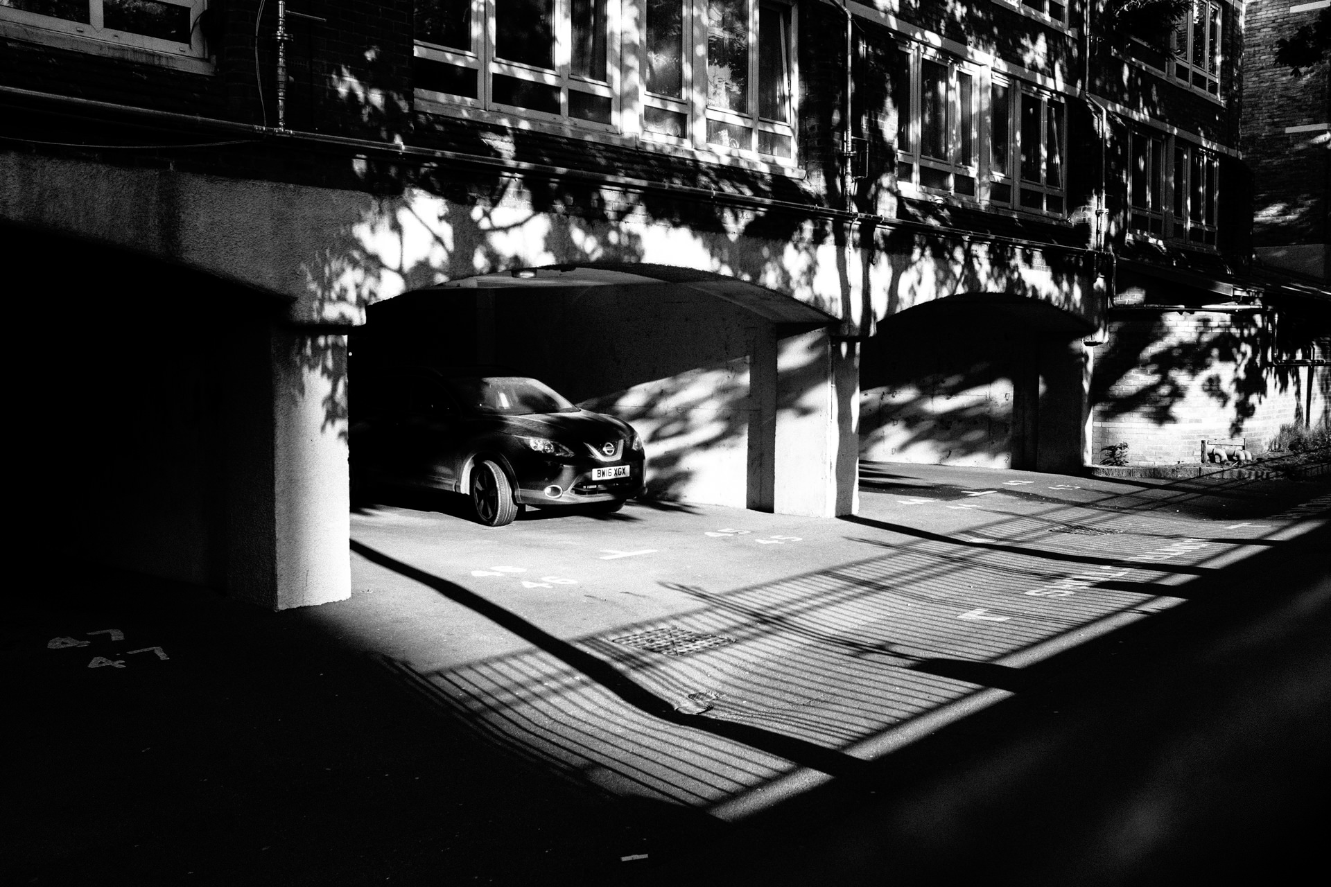 black and white picture of a car parked under the building